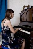 La mujer joven está jugando el piano Foto de archivo