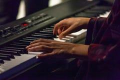 La mujer joven está jugando el piano digital en un pub imagen de archivo libre de regalías