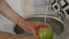 La mujer joven está lavando la manzana verde debajo de golpecito en la cocina casera almacen de metraje de vídeo