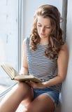 La mujer joven está leyendo el libro Imágenes de archivo libres de regalías