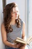 La mujer joven está leyendo el libro Fotos de archivo