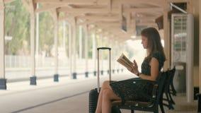 La mujer joven está leyendo un libro que se sienta en un banco en el tren que espera de la estación para almacen de metraje de vídeo