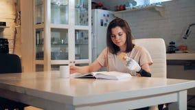 La mujer joven está leyendo un libro y está sosteniendo una galleta con su mano biónica
