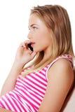 La mujer joven está llamando con un teléfono móvil Fotos de archivo libres de regalías