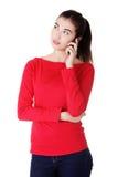 La mujer joven está llamando con un teléfono móvil Foto de archivo libre de regalías