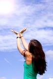 La mujer joven está llevando a cabo sus manos en el cielo Foto de archivo libre de regalías