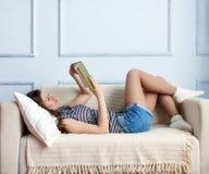 La mujer joven está mintiendo en el sofá Fotografía de archivo libre de regalías