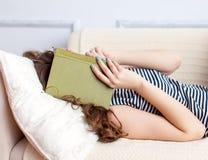 La mujer joven está mintiendo en el sofá Imagenes de archivo