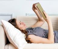 La mujer joven está mintiendo en el sofá Foto de archivo