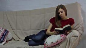La mujer joven está mintiendo en el sofá y el libro de lectura almacen de video