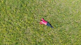 La mujer joven está mintiendo en la hierba en colores amarillos visi?n superior desde la altura almacen de metraje de vídeo