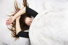 La mujer joven está mintiendo en su cama con los ojos cerrados, sonriendo debajo de su manta después de un sueño relajante fotografía de archivo libre de regalías