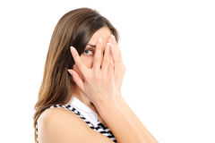 La mujer joven está mirando a través de sus dedos fotos de archivo libres de regalías
