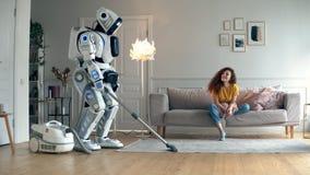La mujer joven está mirando un robot el hoovering de un cuarto metrajes