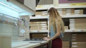 La mujer joven está mirando una superficie de cocinar del horno en una tienda grande metrajes