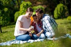 La mujer joven está mostrando las fotos en el teléfono a su marido e hija mientras que se sienta en la manta en el parque imagenes de archivo