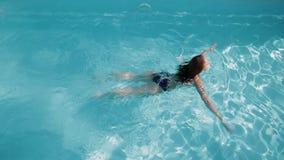 La mujer joven está nadando en la piscina almacen de metraje de vídeo