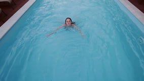 La mujer joven está nadando en la piscina 2 almacen de metraje de vídeo