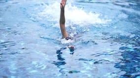 La mujer joven está nadando en una piscina almacen de metraje de vídeo