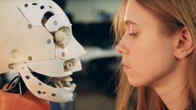 La mujer joven está observando de cerca los movimientos de la cabeza de un cyborg almacen de metraje de vídeo