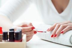 La mujer joven está pintando sus clavos Fotografía de archivo