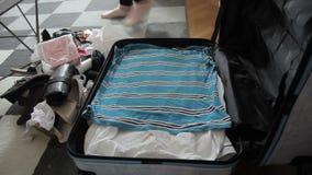 La mujer joven está poniendo la ropa en maleta en sitio en casa almacen de video