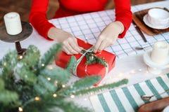 La mujer joven está preparando los regalos para las vacaciones de invierno que vienen Imagenes de archivo