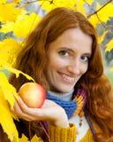 La mujer joven está recorriendo en la madera del otoño imagen de archivo