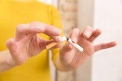 La mujer joven está rompiendo un cigarrillo, abandonó el fumar de concepto Foto de archivo libre de regalías