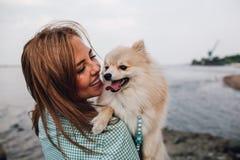 La mujer joven está sosteniendo el perro al aire libre Fotos de archivo libres de regalías
