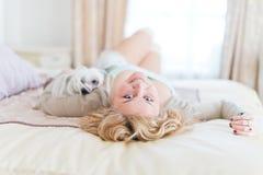 La mujer joven está sosteniendo un perro mientras que pone en una cama Fotos de archivo libres de regalías