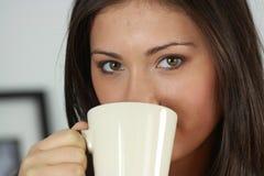 La mujer joven está teniendo su té/café fotografía de archivo
