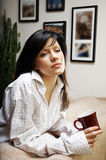 La mujer joven está teniendo té de la mañana Fotos de archivo libres de regalías