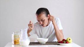 La mujer joven está teniendo un copo de maíz del desayuno con leche y frutas metrajes