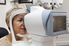 La mujer joven está teniendo un examen médico en el optometrista imagen de archivo libre de regalías