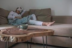 La mujer joven está teniendo un resto en el sofá beige imagen de archivo