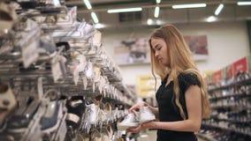 La mujer joven está tomando pares de zapatillas de deporte de moda de los estantes en tienda de zapatos almacen de metraje de vídeo