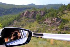 La mujer joven está tomando una foto para el Mountain View de un coche imágenes de archivo libres de regalías