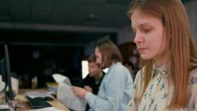 La mujer joven está trabajando en el ordenador en la oficina con su workteam metrajes
