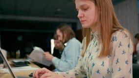 La mujer joven está trabajando en el ordenador portátil en la oficina con su workteam almacen de metraje de vídeo