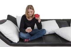 La mujer joven está utilizando el teléfono elegante que sostiene una taza roja Foto de archivo