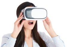 La mujer joven está utilizando las auriculares de VR en el fondo blanco Imagen de archivo