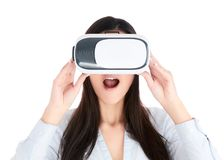 La mujer joven está utilizando las auriculares de VR en el fondo blanco Fotos de archivo