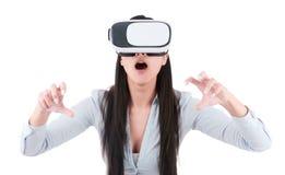 La mujer joven está utilizando las auriculares de VR en el fondo blanco Imagenes de archivo