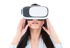 La mujer joven está utilizando las auriculares de VR en el fondo blanco Fotos de archivo libres de regalías