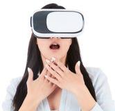 La mujer joven está utilizando las auriculares de VR en el fondo blanco Fotografía de archivo