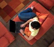 La mujer joven está utilizando una computadora portátil Fotos de archivo libres de regalías
