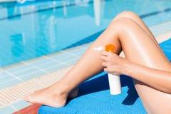 La mujer joven est? aplicando la crema del sol en sus piernas bronceadas lisas por la piscina Factor de protecci?n de Sun en las  foto de archivo libre de regalías