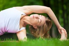 La mujer joven está estirando en el parque Imagenes de archivo