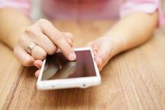 La mujer joven está utilizando el teléfono móvil elegante blanco grande Fotografía de archivo libre de regalías